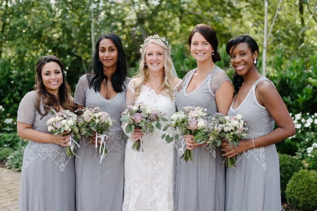 Bride poses with bridesmaids. They wear charcoal grey dresses