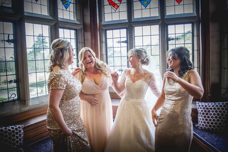 Bride laughing with bridesmaids, wearing gold sequinned dresses