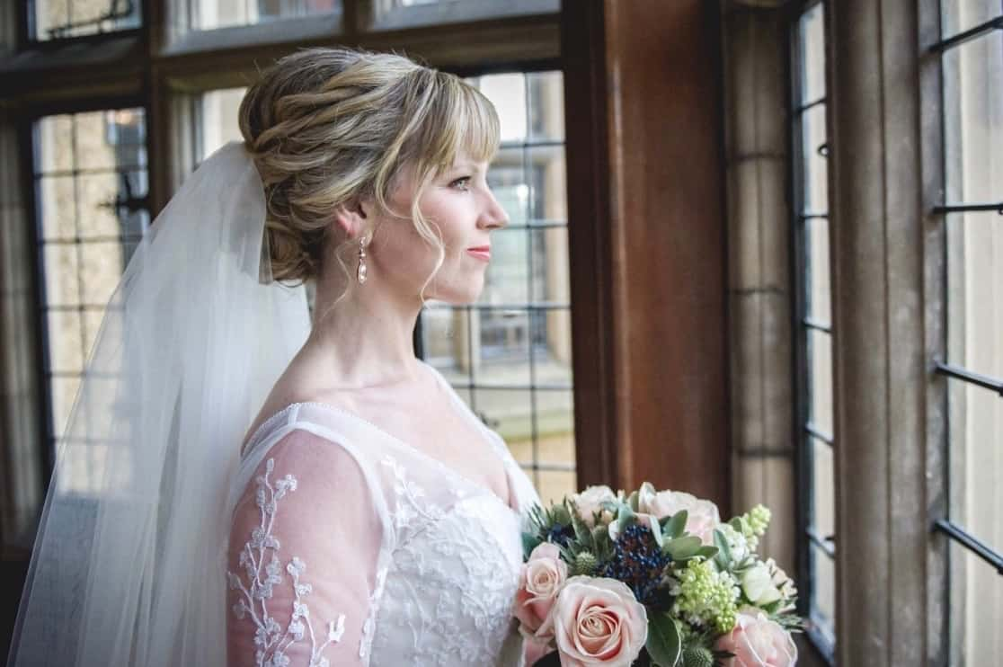 Bride with braided updo looks out of window of Fanhams Hall, Ware, holding bouquet
