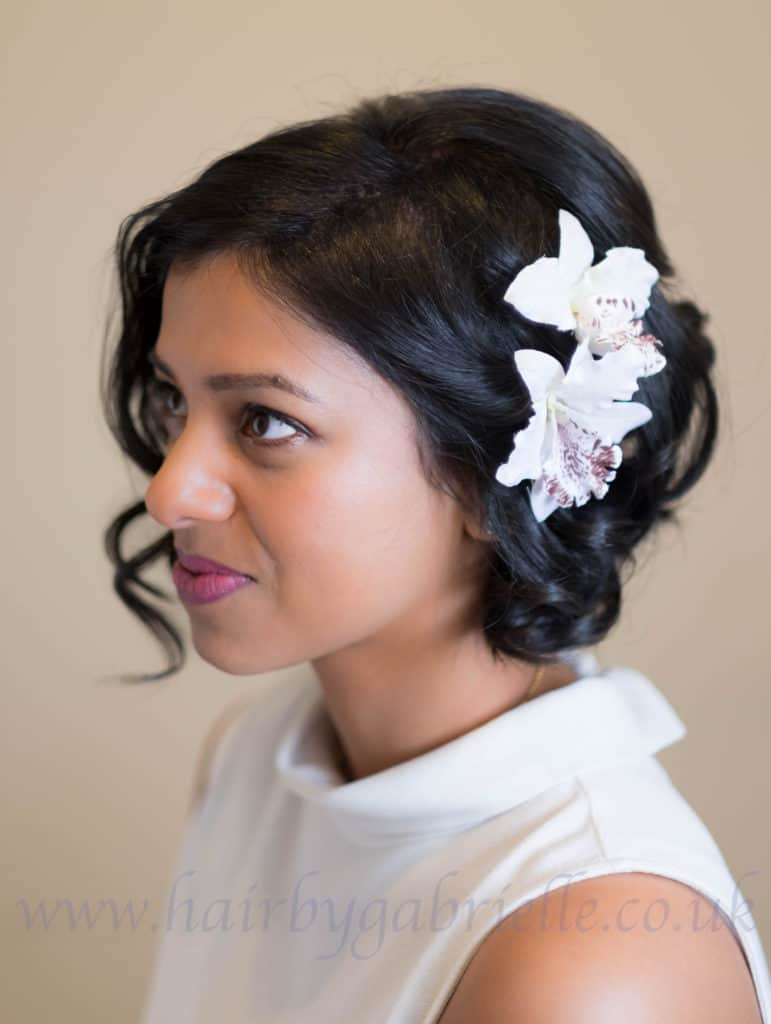 Bride seen in profile with orchids in her hair