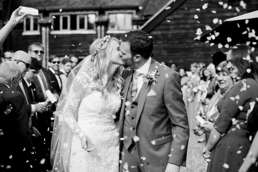 Black and white shot of bride and groom kissing among petal confetti