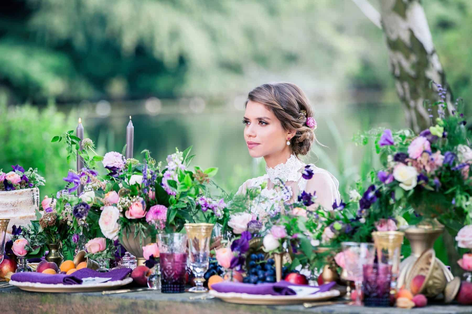 Bridal model seated at table among pink and purple flowers