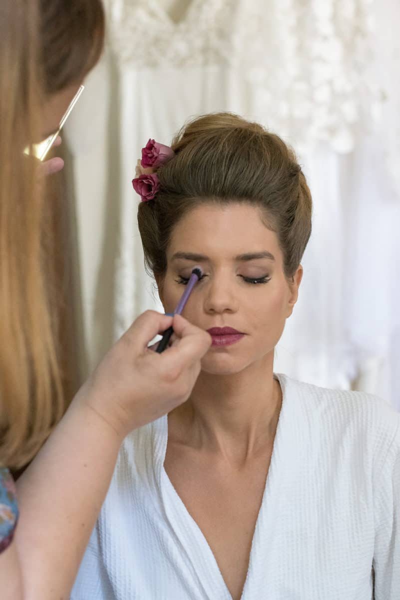 Makeup artist Gabrielle applies eye shadow to a bride on her wedding day