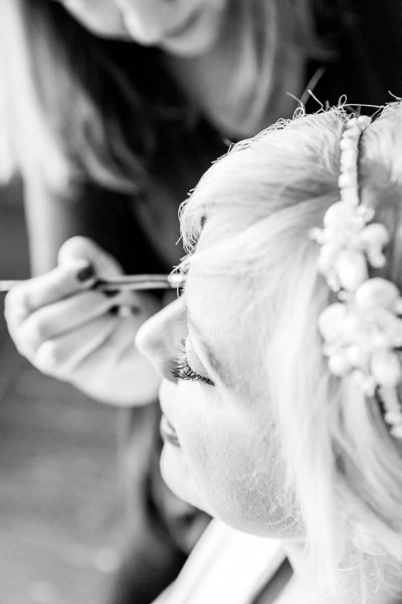 Black and white close up of bride having her make up professionally applied